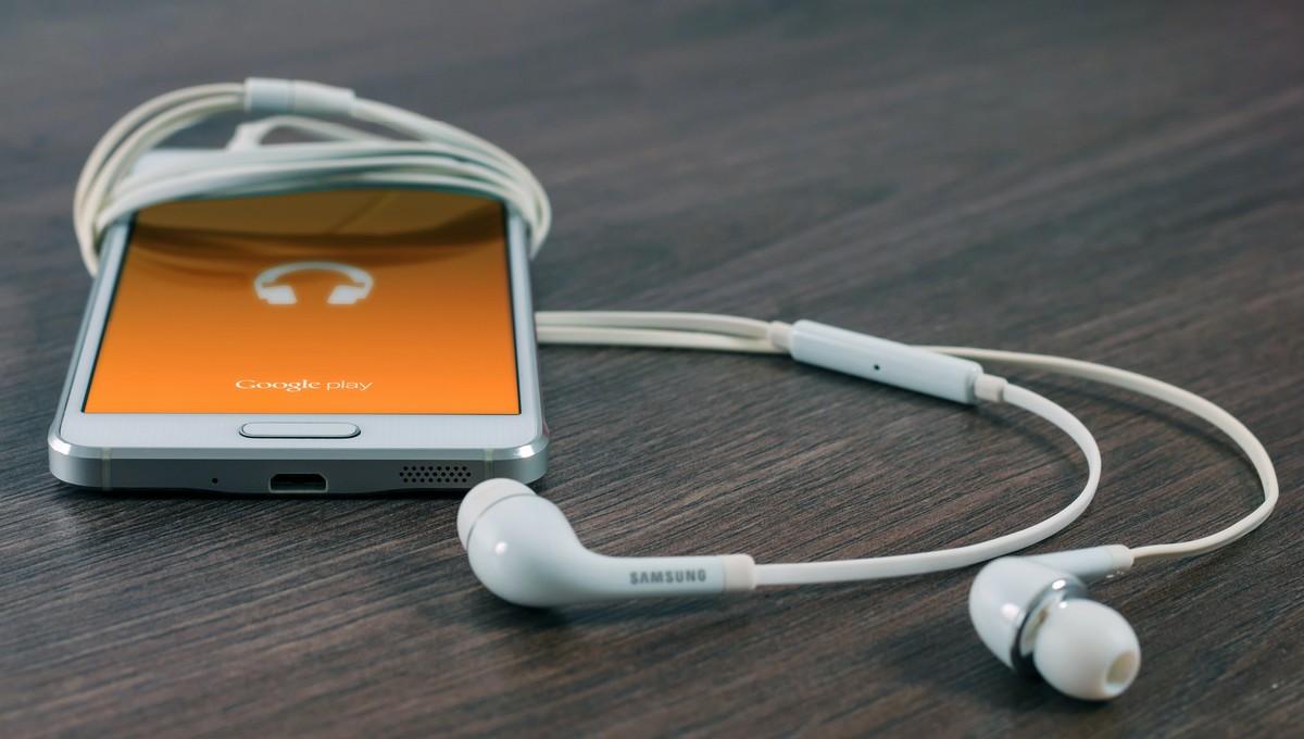 Podcast přehrávaný na mobilním telefonu se sluchátky.